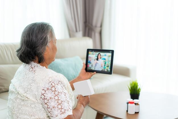 Aziatische senior vrouw met behulp van videoconferentie, online overleg plegen met apotheek