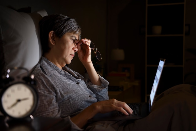 Aziatische senior vrouw met pijnlijke en vermoeide ogen bij het gebruik van een laptop in haar bed 's nachts