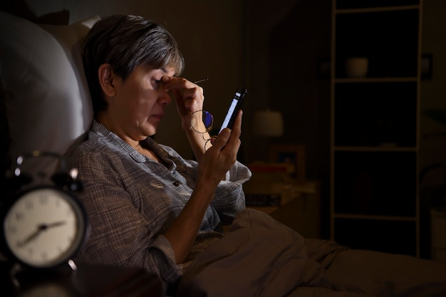 Aziatische senior vrouw met pijnlijke en vermoeide ogen bij het gebruik van smartphone terwijl ze 's nachts in bed ligt