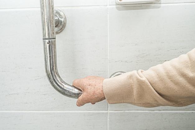 Aziatische senior vrouw patiënt gebruik toilet badkamer handvat beveiliging.