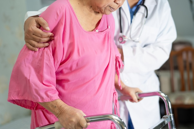 Aziatische senior vrouw patiënt lopen met rollator in het ziekenhuis.