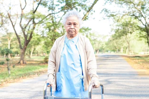 Aziatische senior vrouw patiënt lopen met rollator in park.