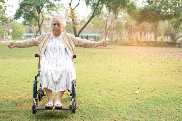 Aziatische senior vrouw patiënt oefening op rolstoel met gelukkig vers genieten in park