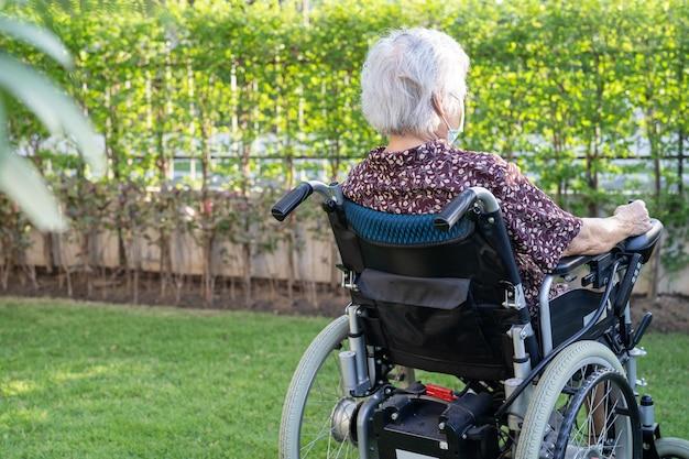 Aziatische senior vrouw patiënt op elektronische rolstoel in park.