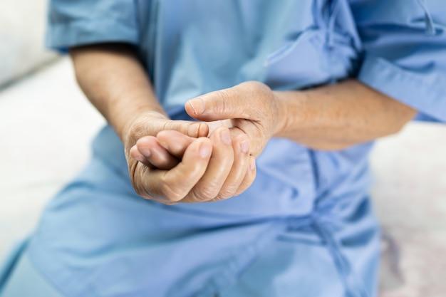 Aziatische senior vrouw patiënt pijn trigger vinger lock haar hand in het ziekenhuis