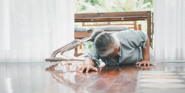 Aziatische senior vrouw vallen op liggende vloer thuis na struikelde op de drempel