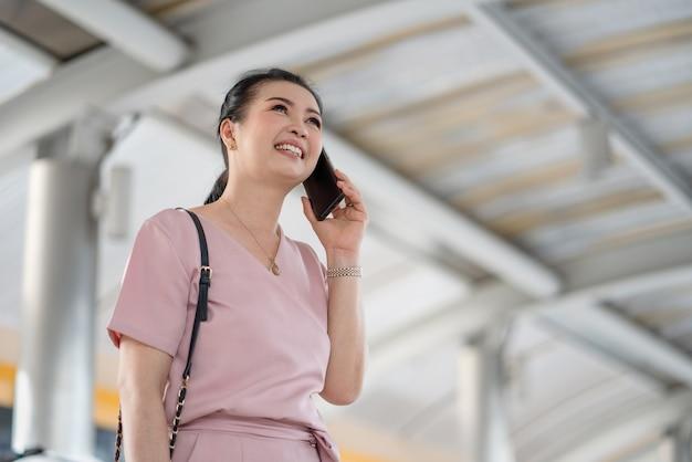 Aziatische senior vrouw zaken praten op smartphone tijdens het wandelen buiten op stad