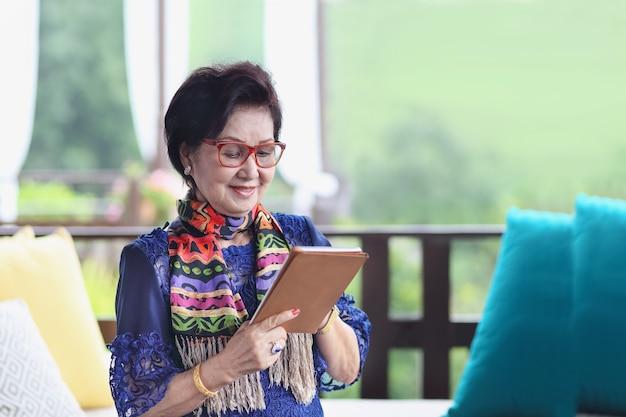 Aziatische senior vrouw zittend op de bank en met behulp van een tablet