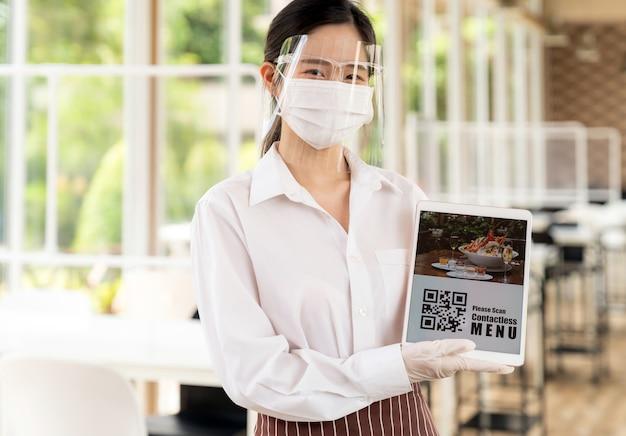 Aziatische serveerster met gezichtsmasker en gezichtsschild houdt digitale tablet met qr-code vast