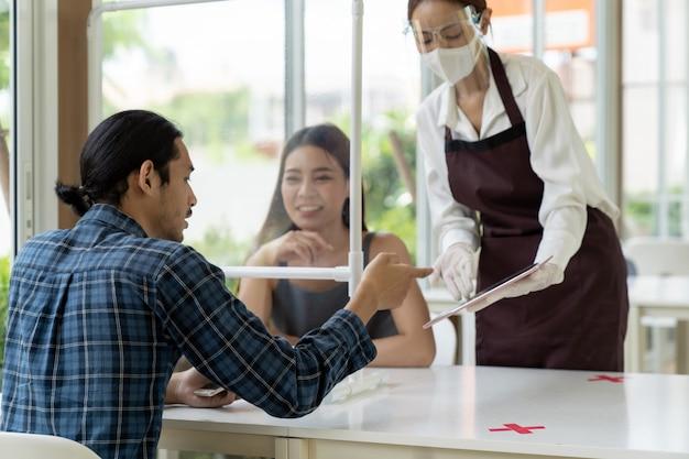 Aziatische serveerster schoen menu met tablet.
