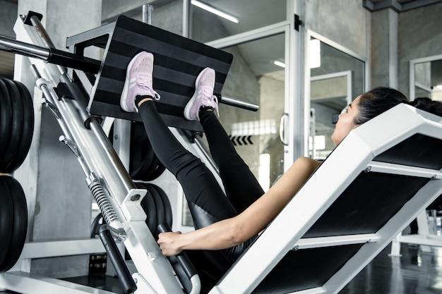 Aziatische sexy vrouw die gewichten speelt met benen op de oefeningsmachine aan de kant van het been in moderne sportschool. fitnessen in de sportschool. zorg voor je gezondheid door te sporten. gezonde zorg met trainingsconcept.