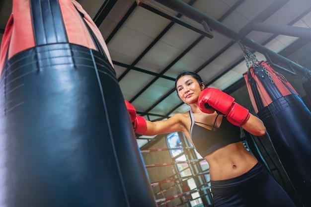 Aziatische sexy vrouw die workoutoefening doet door met zandzak te boksen bij geschiktheidsgymnastiek