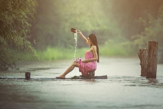 Aziatische sexy vrouwen die in de regen baden
