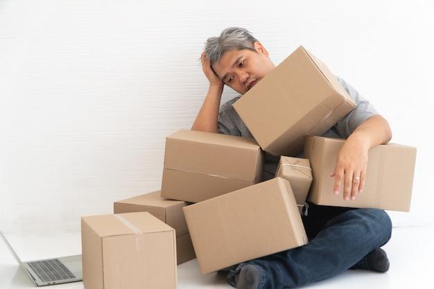 Aziatische shopaholic man geschokt en zittend op de vloer in de woonkamer
