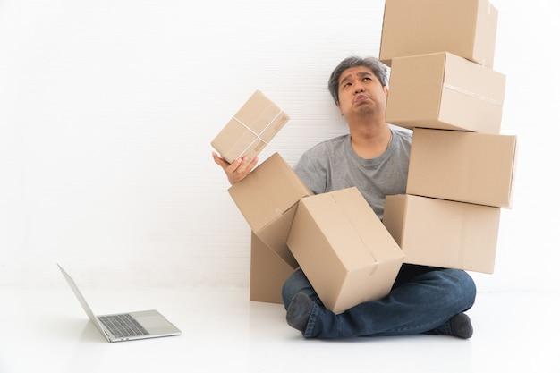 Aziatische shopaholic zittend op de vloer in de woonkamer en kartonnen doos