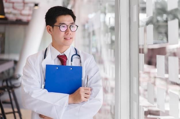 Aziatische slimme artsen bevindende wapens gekruist en holding een blauw documentdossier.