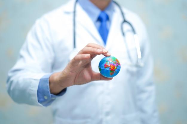 Aziatische slimme mens arts die een bol houdt: gezond sterk medisch concept.