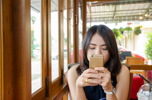 Aziatische smartphone van de vrouwenholding bij koffiekoffie