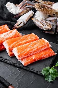 Aziatische snack surimi set, op stenen bord, op zwarte tafel