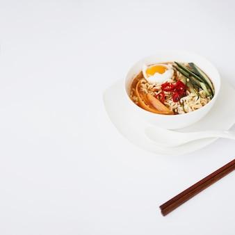 Aziatische soep en eetstokjes op wit