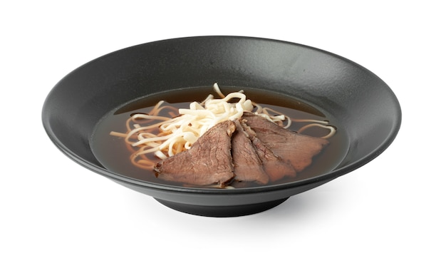 Aziatische soep met rundvlees en udon-noedels die op wit worden geïsoleerd