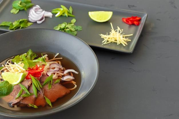 Aziatische soep ramen geserveerd in zwarte kom op grijze tafel close-up