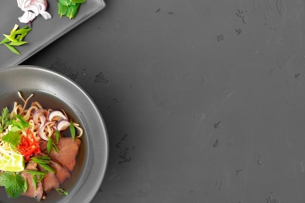 Aziatische soep ramen met varkensvlees en noedels wordt geserveerd op een grijze tafelbladweergave