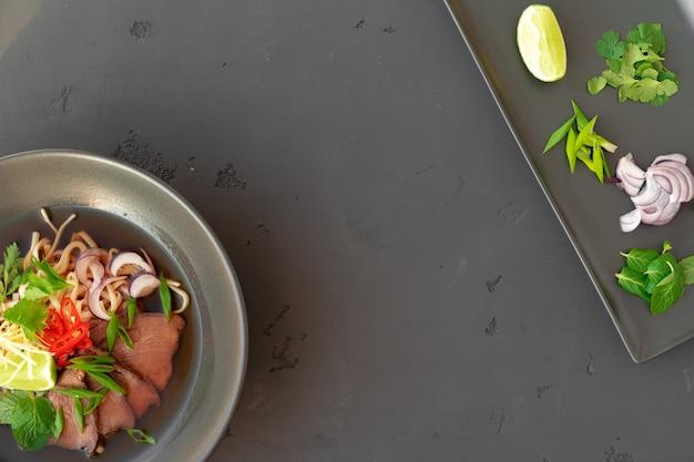 Aziatische soep ramen met varkensvlees en noedels wordt geserveerd op grijze bovenaanzicht als achtergrond
