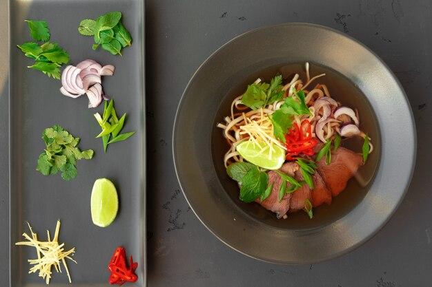 Aziatische soep ramen met varkensvlees en noedels wordt op een grijze achtergrond geserveerd