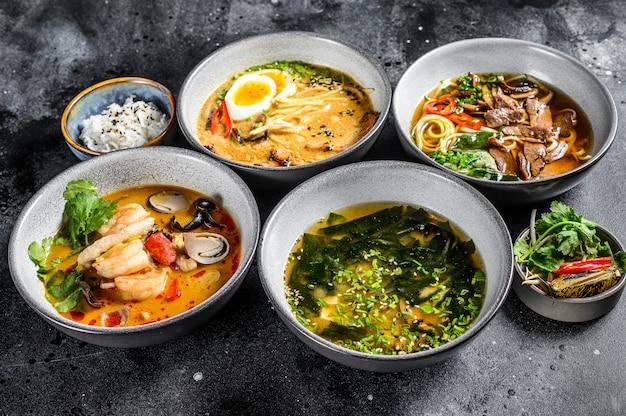Aziatische soepen, miso, ramen, tom yam, pho bo. zwarte achtergrond. bovenaanzicht