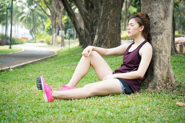 Aziatische sport vrouw rust op grasland in park na het lopen