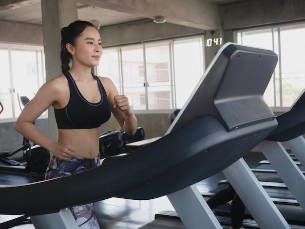 Aziatische sportenvrouwen bij het lopen in gymnastiek, geschiktheidsconcept