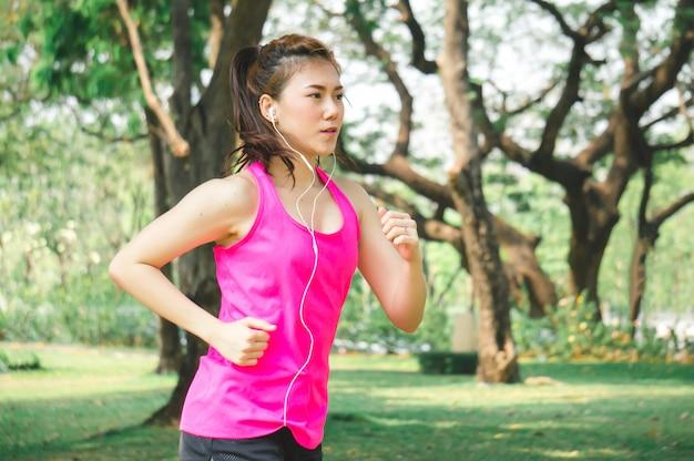 Aziatische sportvrouw die / in park lopen aanstoten