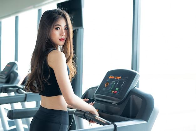 Aziatische sportvrouw die of op tredmolenmateriaal lopen lopen in de gymnastiek van de geschiktheidstraining