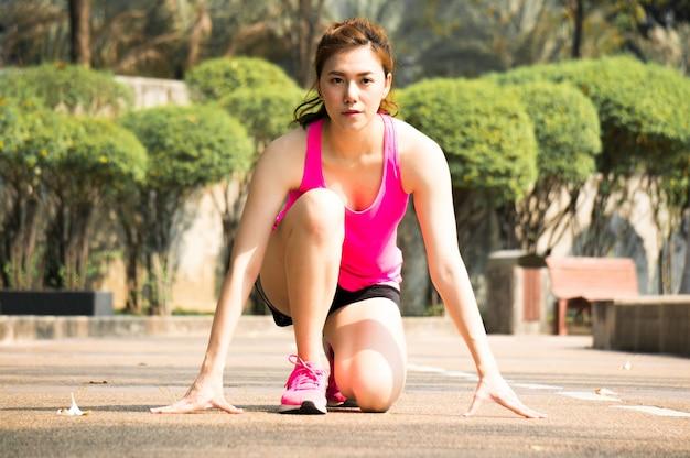 Aziatische sportvrouw klaar om op beginpunt in park te lopen