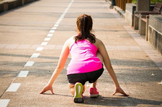Aziatische sportvrouw klaar op beginpunt voor het lopen