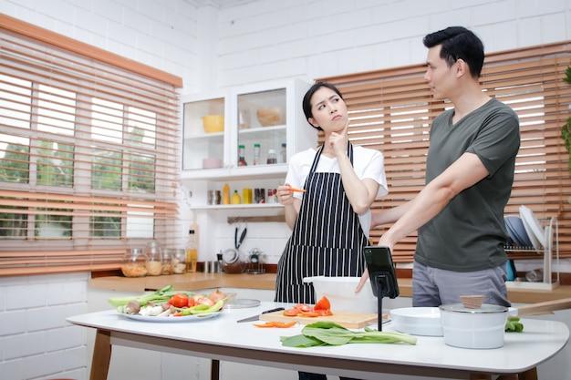 Aziatische stellen hebben het plezier om thuis in de keuken te koken