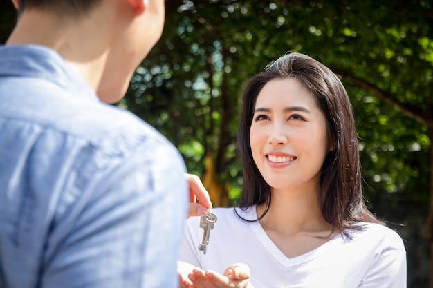 Aziatische stellen kopen huizen om bij elkaar te blijven. mannen geven huissleutels aan vrouwen. het concept van het starten van een gelukkig gezin