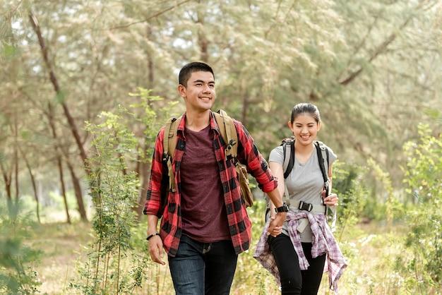 Aziatische stellen, mannen die elkaars hand vasthouden, vrouwen die gelukkig wandelen tijdens het reizen in het bos