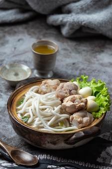 Aziatische stijl soep met noedels, varkensvlees en groene uien nauw in een kom op tafel.