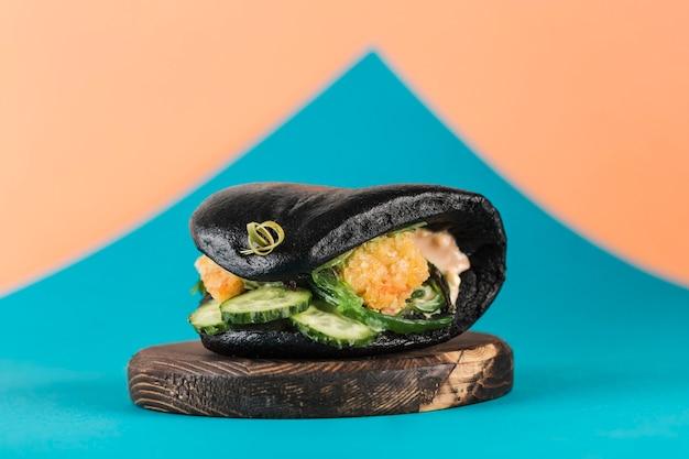 Aziatische straat fastfood-bao burger met gepaneerde garnalen, verse komkommers en zeewier in een zwarte inktvis
