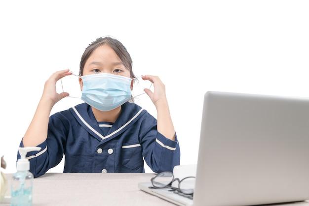 Aziatische student die chirurgisch masker draagt en geïsoleerde studeert computer, e-learning en covid-19 of coronavirus quarantaine.