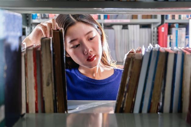 Aziatische student die in toevallig kostuum het boek in ernstig gevoel van boekenplank zoeken in bibliotheek van universiteit