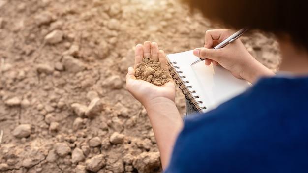 Aziatische student die onderzoek doet of droge grond in leeg land controleert voor het planten