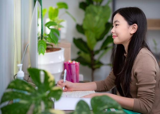 Aziatische student die thuis door computer en internet leert
