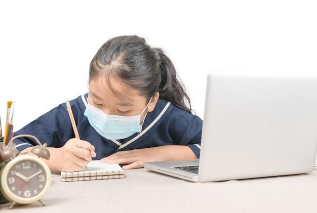 Aziatische student draagt beschermend masker, maakt aantekeningen van laptop, schrijft huiswerk, nieuwe normaal en voorkomt covid 19-infectie