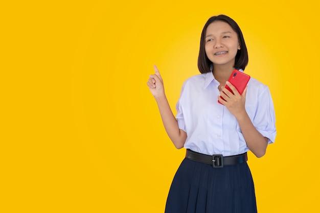 Aziatische student in uniform gebruik rode slimme telefoon.