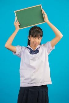 Aziatische student met lang haarmeisje die een groene raad op een blauw houden.