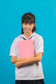 Aziatische student met lang haarmeisje die een notitieboekje op een blauw houden.