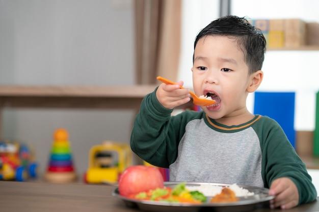 Aziatische student neemt een lunch in de klas door een dienblad met voedsel dat door zijn kleuterschool is bereid